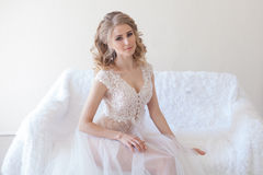 Beautiful girl in lingerie sitting on a white couch wedding Royalty Free Stock Photos