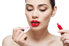 Beautiful girl with lipgloss. Beautiful young woman applying red lipgloss with applicator. Isolated over white background. Copy space Royalty Free Stock Image