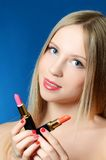 The beautiful girl with lipsticks in hands Royalty Free Stock Photos