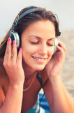 Beautiful girl listening music on the beach Royalty Free Stock Photo
