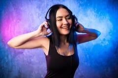 Beautiful girl listening music in big headphones stock image