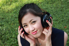 Beautiful girl listening music in the park Royalty Free Stock Photography