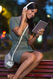 Beautiful girl listening to music in the city at night. Royalty Free Stock Photo