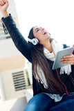 Beautiful girl listening to music in city. Royalty Free Stock Photo
