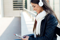 Beautiful girl listening to music in city. Stock Photo