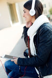 Beautiful girl listening to music in city. Royalty Free Stock Photos