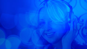 Beautiful girl listening to music with headphones, blue bokeh light background Stock Image