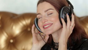 Beautiful girl listening to music on headphones with closed eyes. stock video footage