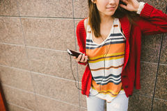 Beautiful girl listening to music with headphones holding a smart phone, the player in the hand. Dressed in a red jacket and jeans Stock Photos