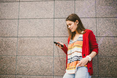 Beautiful girl listening to music with headphones holding a smart phone, the player in the hand. Dressed in a red jacket and jeans Royalty Free Stock Photo
