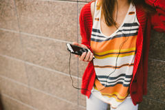 Beautiful girl listening to music with headphones holding a smart phone, the player in the hand. Dressed in a red jacket and jeans Royalty Free Stock Photos