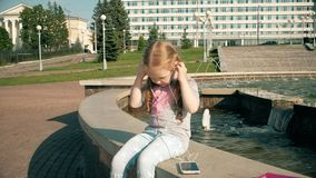 Beautiful girl listening to music on headphones with phone near fountain stock video