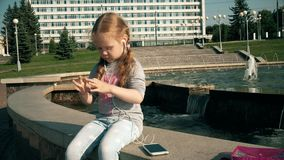 Beautiful girl listening to music on headphones with phone near fountain. 4k stock footage