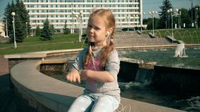 Beautiful girl listening to music on headphones with phone near fountain stock footage