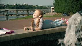 Beautiful girl listening to music on headphones with phone near fountain stock video footage