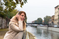 Beautiful girl listening to music with headphones in an urban co Royalty Free Stock Image
