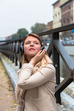 Beautiful girl listening to music with headphones in an urban co Stock Images