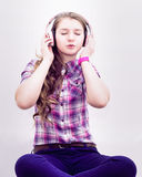 Beautiful girl listening to music on headphones royalty free stock photography
