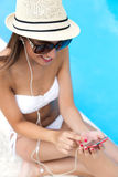 Beautiful girl listening to music in the swimming pool. Royalty Free Stock Photos