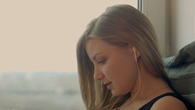 Beautiful girl listening to music with tablet at stock video footage