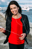 Beautiful girl listening to music on the waterfront Stock Image