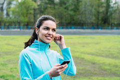 Beautiful girl listening to music before a workout. Girl tuned to sports and listening to music Royalty Free Stock Photo