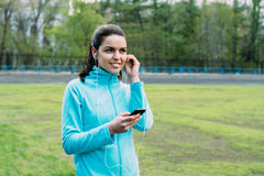 Beautiful girl listening to music before a workout. Girl tuned to sports and listening to music Stock Photography