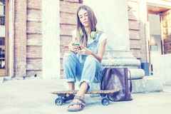 Beautiful girl listens to music on his smartphone Royalty Free Stock Photos