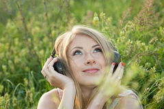 Beautiful girl listens to music in the meadow. One of the photos Made during a photo shoot of Russian girl in summer at sunset Stock Image