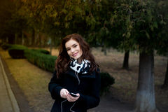 Beautiful girl listens to music in the park Stock Photos