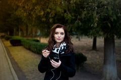 Beautiful girl listens to music in the park royalty free stock photography