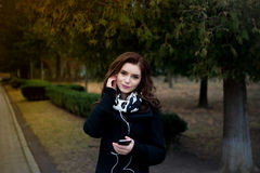 Beautiful girl listens to music in the park Royalty Free Stock Images
