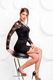 Beautiful girl in a little black dress on a chair Royalty Free Stock Photography