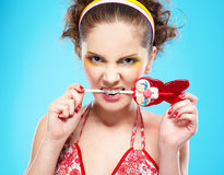 Beautiful girl with lollipop. Portrait of beautiful slavonic girl posing with red bunny-lollipop and jokingly biting it Stock Images