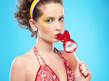 Beautiful girl with lollipop. Portrait of beautiful slavonic girl tasting red bunny-lollipop Stock Photography