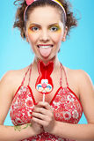 Beautiful girl with lollipop. Portrait of beautiful slavonic girl posing with red bunny-lollipop and jokingly showing tongue Royalty Free Stock Photography