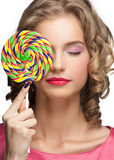 Beautiful girl with lollipop. Portrait of beautiful girl with blond curly hair holding lollipop Stock Image