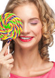 Beautiful girl with lollipop. Portrait of beautiful girl with blond curly hair holding lollipop Royalty Free Stock Images