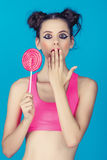 Beautiful girl with a lollipop and a bright pink shirt. Surprised Royalty Free Stock Photo