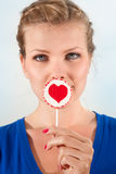 Beautiful girl with lollipop heart in her hand. Portrait beautiful young blond girl with lollipop heart in her hand Royalty Free Stock Image