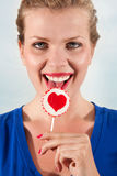 Beautiful girl with lollipop heart in her hand. Portrait beautiful young blond girl with lollipop heart in her hand Stock Image