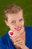 Beautiful girl with lollipop heart in her hand. Portrait beautiful young blond girl with lollipop heart in her hand Royalty Free Stock Photo