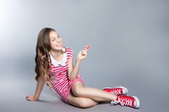 Beautiful girl with a lollipop in her hand is posing on a gray background. girl in a dress in red with white stripes. fashion tast. E Royalty Free Stock Photography