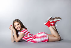 Beautiful girl with a lollipop in her hand is posing on a gray background. girl in a dress in red with white stripes. fashion tast. E Stock Photography