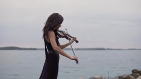 Beautiful girl in black dress plays violin at sea background. Art concept in 4k stock video footage