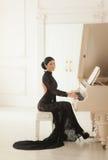 Beautiful girl in a long black dress stock photos