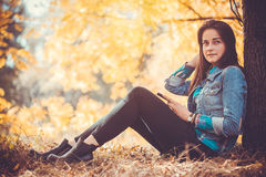 Beautiful girl with long black hair in the autumn park Stock Image