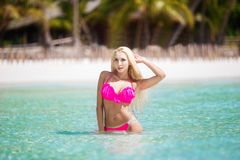 Beautiful girl with long blond hair in bikini on the shore of a Royalty Free Stock Image