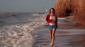 A beautiful girl with long blond hair, in a red jacket, with unusual, rectangular purple glasses, a chain, denim shorts. With bare feet, a striped T-shirt runs stock footage
