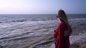 A beautiful girl with long blond hair, in a red T-shirt, looks down from a mountain of clay, on a flat horizon, a blue stock video